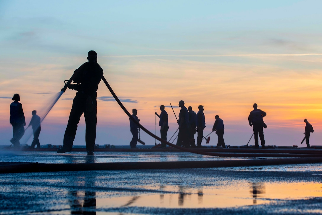 A sailor shown in silhouette uses a hose to spray down the deck of a ship as others stand in the background holding brooms.