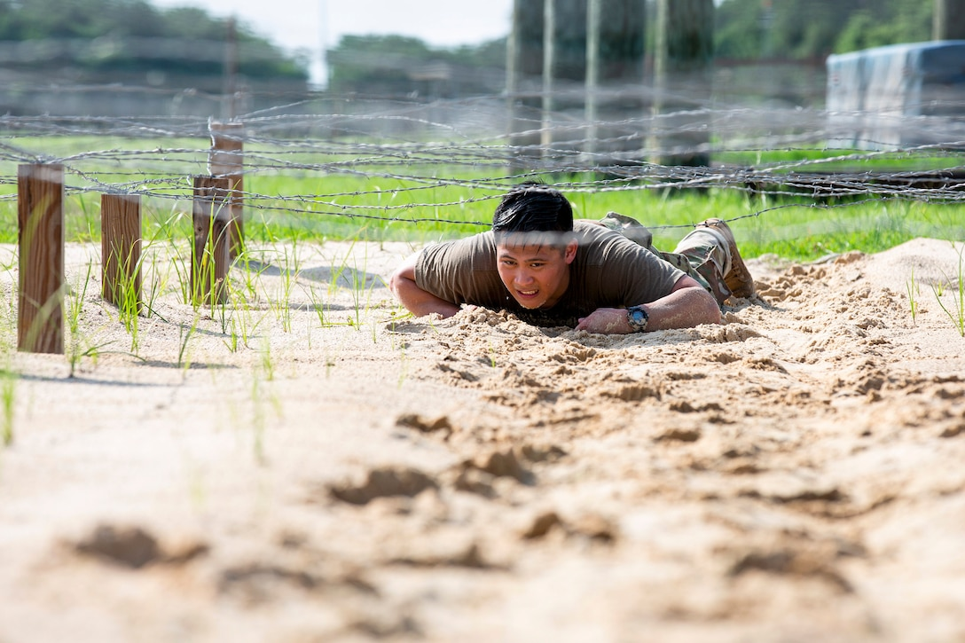 A soldier low-crawls in sand under barbed wire.