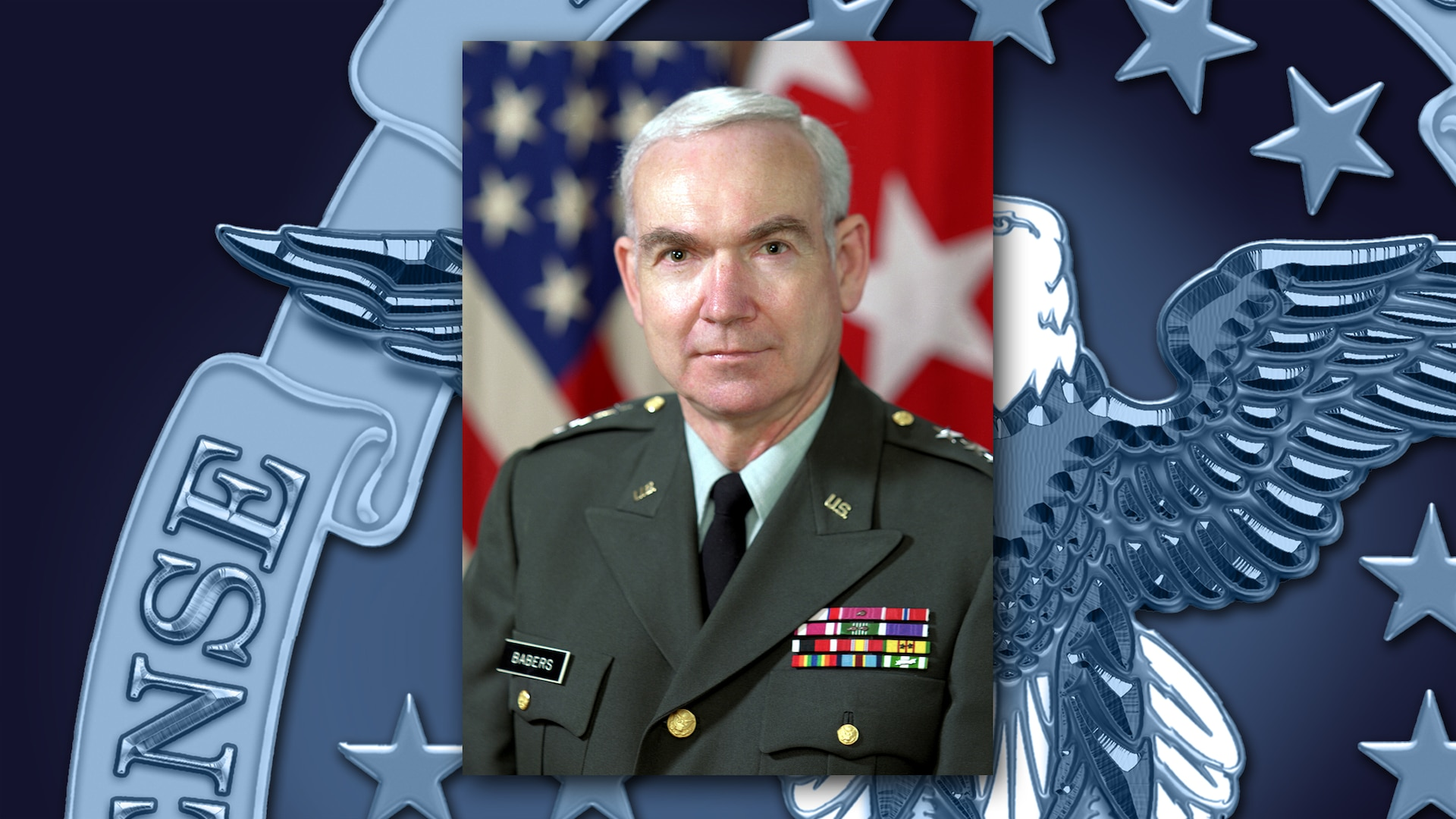 White man in Army green dress uniform with ribbons stands in sits in front of the US flags.