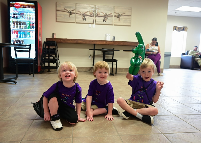 Three children sit on the floor while smiling.