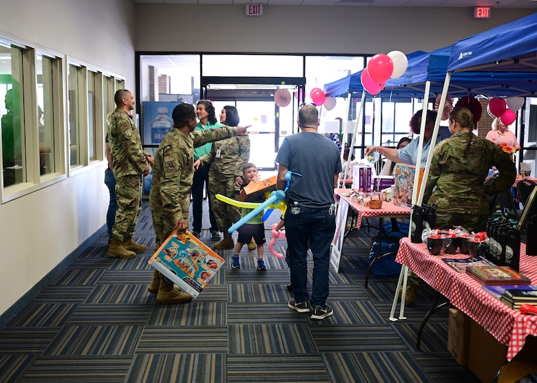 Airmen and families stand near blue tents with tables under them that contain gifts and information.