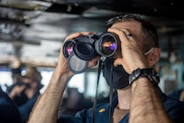 Lt. Cmdr. Bill Zincicolalapin, from Nutley, New Jersey, uses binoculars to look for surface contacts on the bridge of the Nimitz-class aircraft carrier USS Harry S. Truman (CVN 75) during Tailored Ship's Training Availability (TSTA) and Final Evaluation Problem (FEP).
