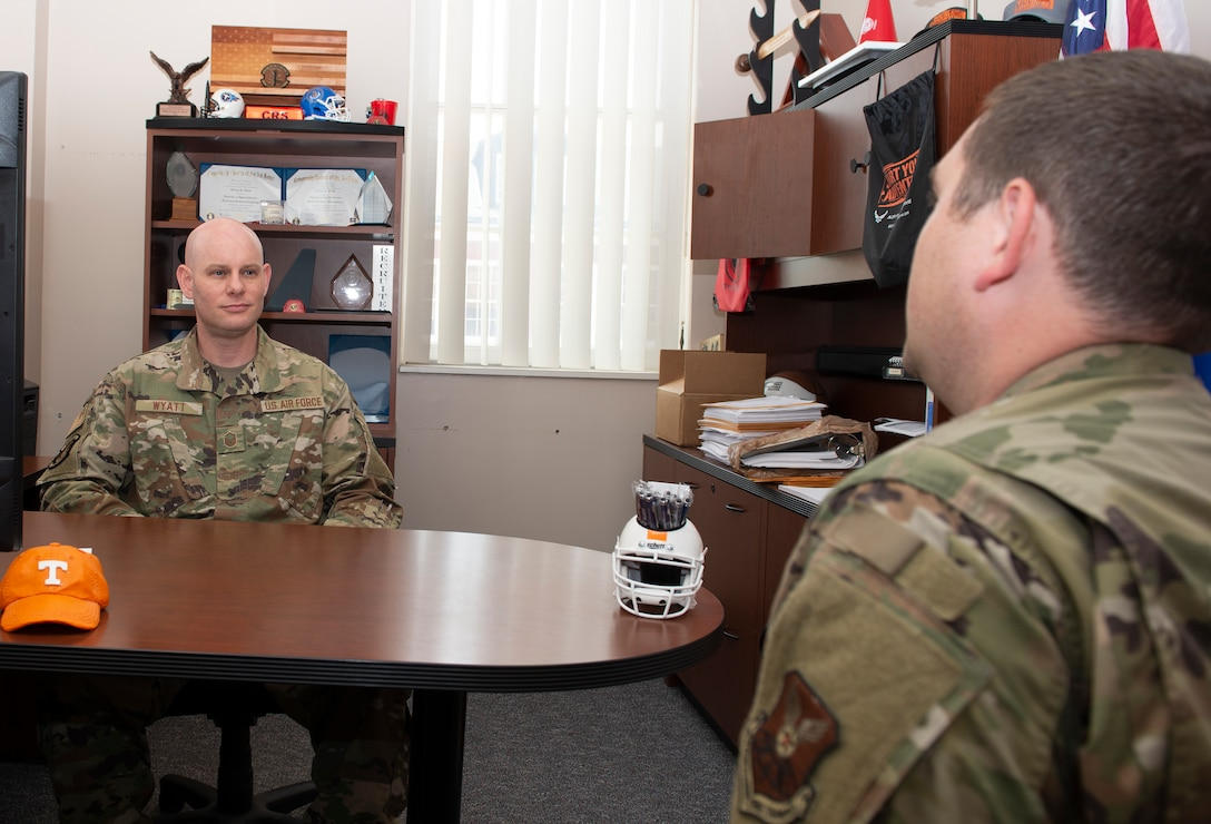 Master Sergeant sitting behind a desk in his office, listening to Airmen seated in front of the desk