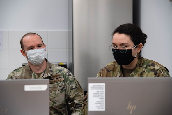 U.S Air Force Capt. Michael Jacobs, deputy branch chief of future operations headquarters United States European Command, discusses with Staff Sgt. Janeace Stampul, 2d Communication Squadron Mission Defense Team technician, about the capabilities of their Mission Assurance Capabilities Kit at Morón Air Base, Spain, June 2, 2021. Mission Defense Teams safeguard data analytics ensuring   weapons systems are safe from adversaries. (U.S. Air Force photo by 2nd Lt Aileen Lauer)