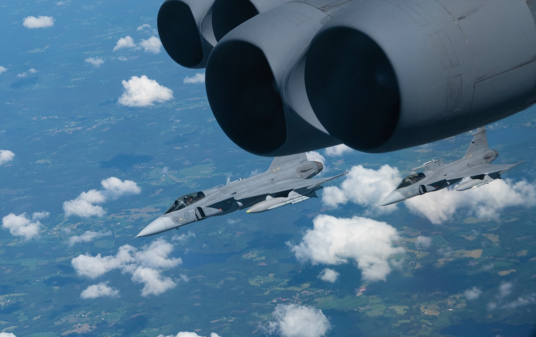 Two Swedish Saab JAS-39 Gripen fighter jets escort a B-52H Stratofortress over Europe during a Bomber Task Force Europe 21-3 flight en route to a maritime training scenario, June 09, 2021.