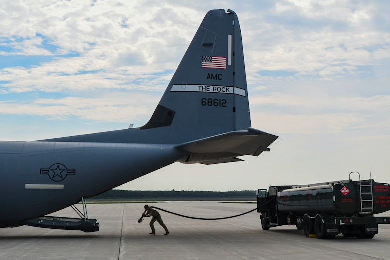 An Airman from the 19th Logistics Readiness Squadron pulls a hose from a fuel truck