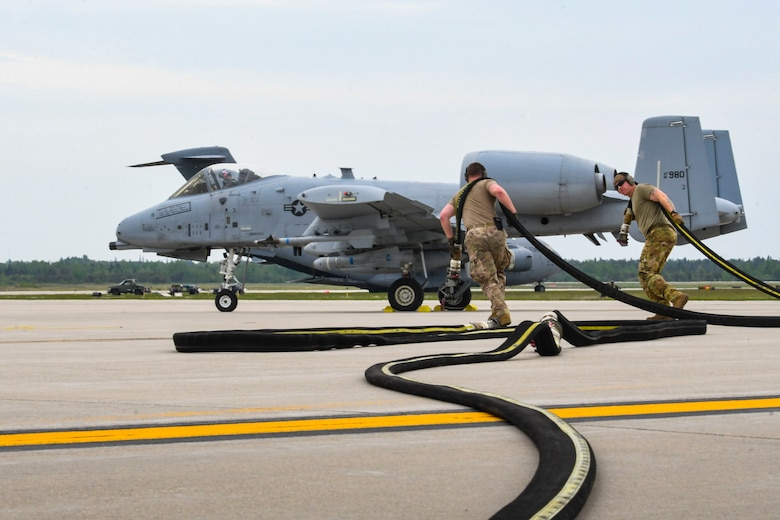 Airmen from the 19th Airlift Wing prepare for refueling near a U.S. Air Force A-10 Thunderbolt II