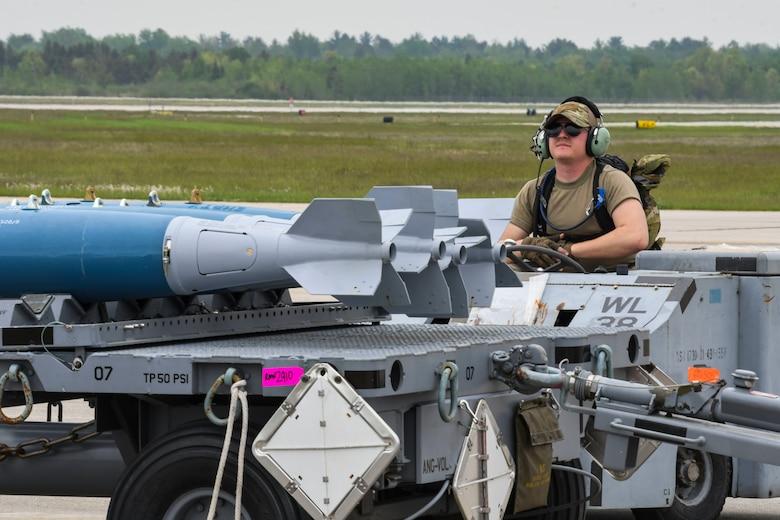 An Airman from the 354th Aircraft Maintenance Unit drives a MHU-83 Bomb Lift