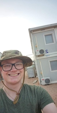 Senior Airman Caleb S. Kimmell smiles outside of his containerized living unit for his first deployment selfie. Kimmell arrived in Africa for his first deployment as a public affairs journeyman for the 435th Air Expeditionary Wing. (U.S. Air Force photo by Senior Airman Caleb S. Kimmell)