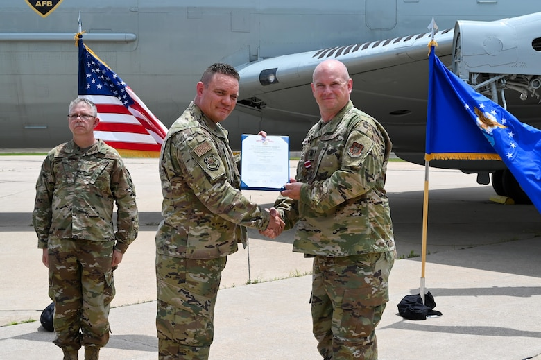 Lt. Col. Stan Young, 507th Mission Support Group commander, presents Lt. Col. Dustin Born, 507th Civil Engineer Squadron former commander, a meritorious service medal during an outdoor change of command ceremony on the flightline June 6, 2021, at Tinker Air Force Base, Oklahoma. (U.S. Air Force photo by Senior Airman Mary Begy)