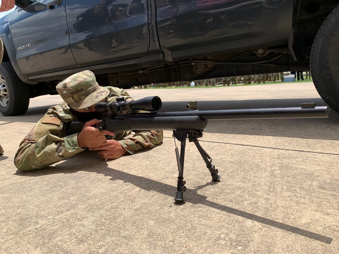 Airman lying on ground looking through rifle scope.