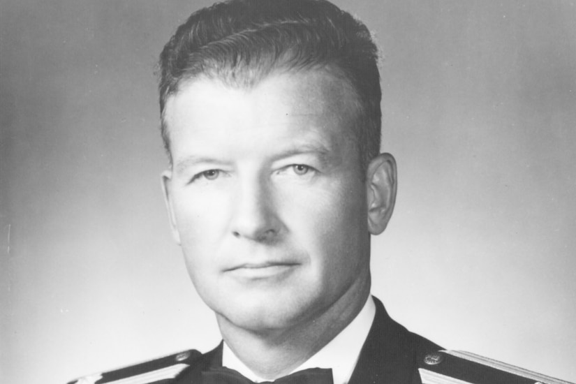 A man in a formal military uniform poses for the camera.