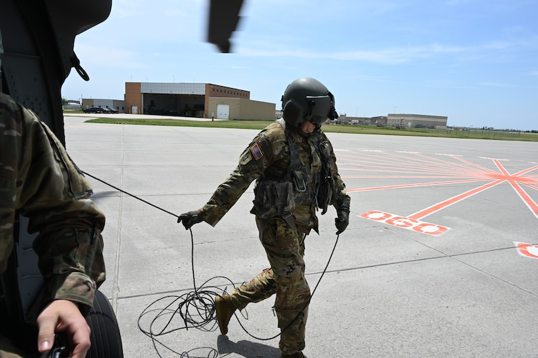 Staff Sgt. Andrew Iverson, a crew chief in the 1st Battalion, 112th Aviation Regiment, North Dakota Army National Guard, works around a UH-60 helicopter as it lands at the North Dakota Air National Guard Base, Fargo, N.D., June 8, 2021. Airmen aboard the helicopter are simulating arrival at a high-threat area for training. (U.S. Air National Guard photo by Chief Master Sgt. David H. Lipp)