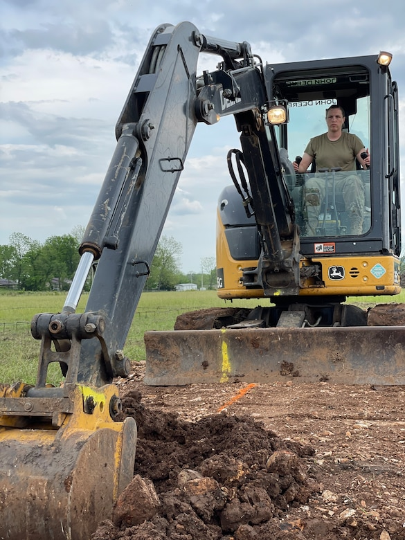 Tech. Sgt. Katie Cramer, with the 176th Wing's Civil Engineer Squadron Heavy Equipment Shop, digs a trench with a mini-excavator in preparation for pouring concrete footers on home site six while participating in the Cherokee Veterans Housing Initiative in Tahlequah, Oklahoma, May 26, 2021. The initiative is a collaboration between the Department of Defense's Innovative Readiness Training program and the Cherokee Nation that constructs new single-family homes and supporting infrastructure for eligible Cherokee Nation veterans and their families.  (U.S. Air Guard photo by Senior Master Sgt. Michael Keegan)