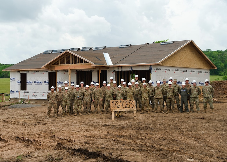 Alaska Air National Guardsmen with the 176th Civil Engineer Squadron stand alongside Brig. Gen. Anthony Stratton, 176th Wing commander, as they near the end of their participation in the Cherokee Veterans Housing Initiative in Tahlequah, Oklahoma, May 27, 2021. The initiative is a collaboration between the Department of Defense's Innovative Readiness Training program and the Cherokee Nation that constructs new single-family homes and supporting infrastructure for eligible Cherokee Nation veterans and their families.  (U.S. Air Guard photo by Staff Sgt. Clay Cook)