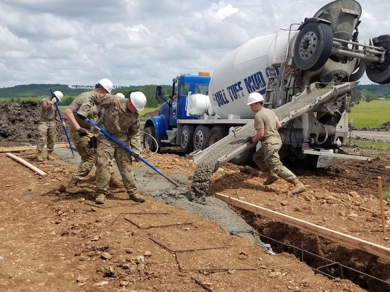 Tech. Sgt. Katie Cramer, right, with the 176th Wing's Civil Engineer Squadron, leads the crew while placing and finishing 18 cubic yards of concrete for the footers on home site number six during the Cherokee Veterans Housing Initiative in Tahlequah, Oklahoma, May 24, 2021. The initiative is a collaboration between the Department of Defense's Innovative Readiness Training program and the Cherokee Nation that constructs new single-family homes and supporting infrastructure for eligible Cherokee Nation veterans and their families. (U.S. Air Guard photo by Staff Sgt. Clay Cook)
