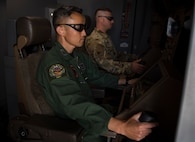 Japan Air Self-Defense Force Chief Master Sgt. Teruyuki Mizokami, 405th Air Refueling Squadron senior boom-operator, simulates operating a KC-46 Pegasus boom, May 13, 2021, at Altus Air Force Base, Oklahoma. The KC-46 boom operator is seated in the front of the aircraft while operating the boom instead of in the back as with other refuelers, such as the KC-135 and KC-10. (U.S. Air Force photo by Airman 1st Class Amanda Lovelace)