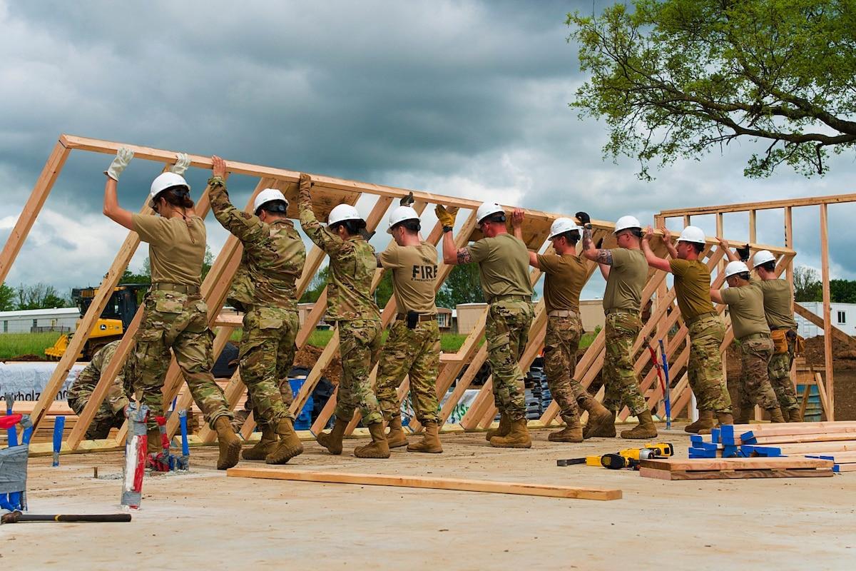 Airmen raise an exterior wall.