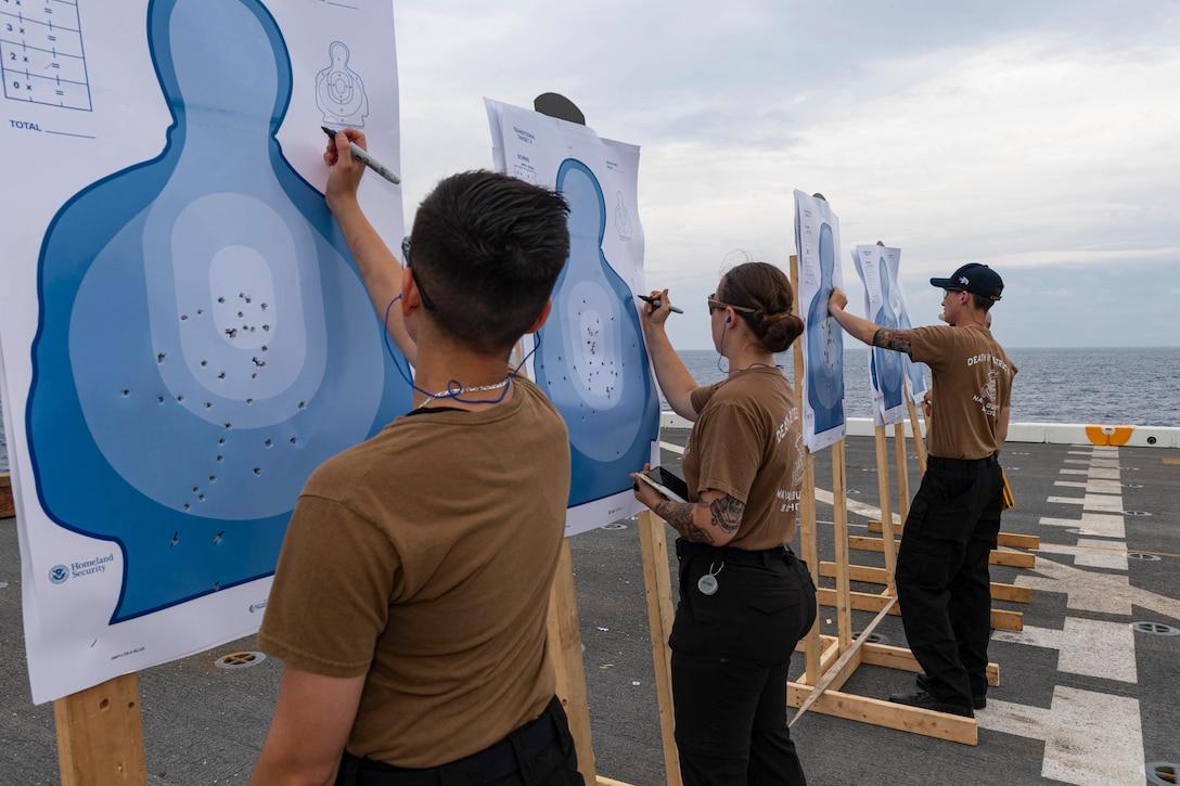 Sailors write on shooting targets.