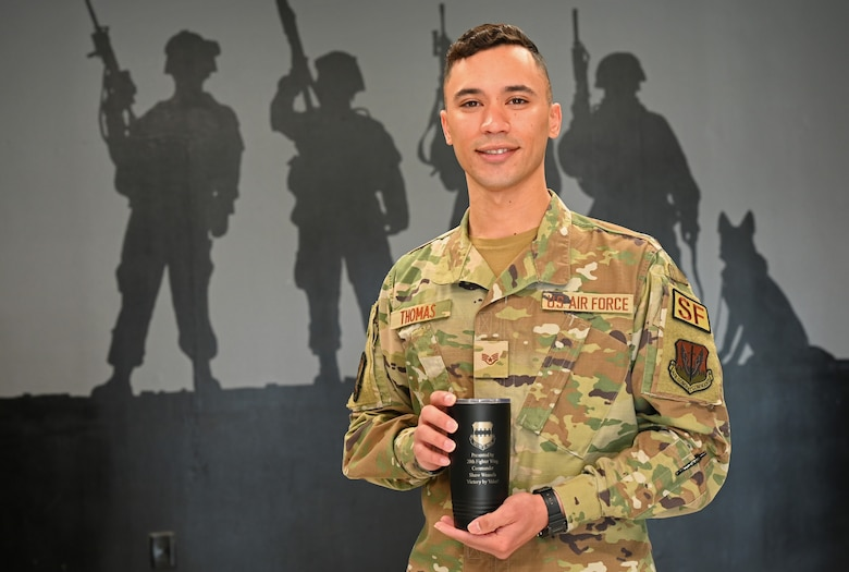 A photo of SSgt Thaddeus Thomas holds mug in front of mural.