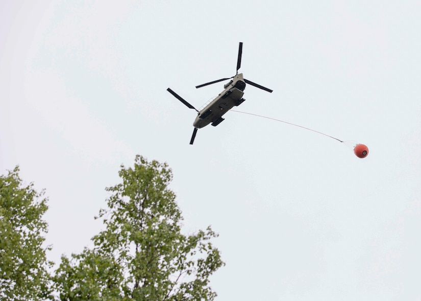 A 1st Battalion, 207th Aviation Regiment CH-47 Chinook helicopter with a Bambi water bucket system attached flies overhead during the unit's Red Card certification on Joint Base Elmendorf-Richardson, June 9, 2021. Red Card certification, also known as the Incident Qualification Card, is an accepted interagency certification that a person is qualified in order to accomplish the required mission when arriving on an incident. For 1-207th AVN pilots, this certification means proficiency in water bucket drops to assist with wildfire emergencies within the state. (U.S. Army National Guard photo by Spc. Grace Nechanicky)