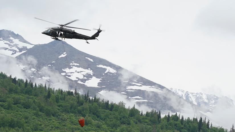 A 1st Battalion, 207th Aviation Regiment UH-60 Black Hawk helicopter with a Bambi water bucket system attached flies overhead during the unit's Red Card certification on Joint Base Elmendorf-Richardson, June 9, 2021. Red Card certification, also known as the Incident Qualification Card, is an accepted interagency certification that a person is qualified in order to accomplish the required mission when arriving on an incident. For 1-207th AVN pilots, this certification means proficiency in water bucket drops to assist with wildfire emergencies within the state. (U.S. Army National Guard photo by Dana Rosso)