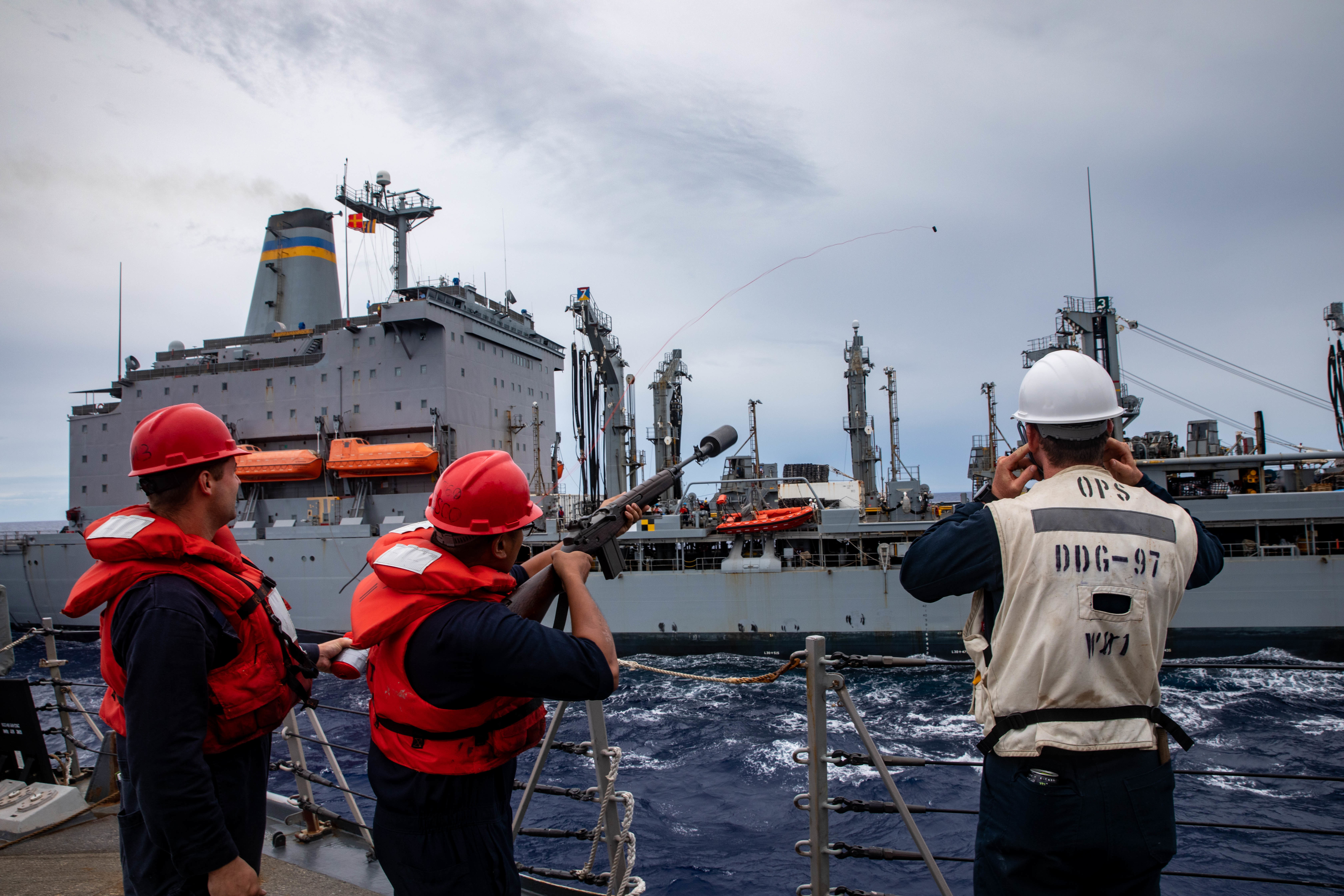 Gunner's Mate 2nd Class Andrew Escomiendo, from Vista, Calif., fires a shot line aboard the Arleigh Burke-class guided-missile destroyer USS Halsey (DDG 97) to the Henry J. Kaiser-class underway replenishment oiler USNS Rappahannock (T-AO-204) during a replenishment-at-sea aboard the Arleigh Burke-class guided-missile destroyer USS Halsey (DDG 97).