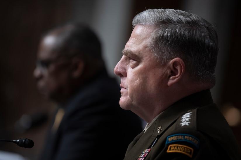 Secretary of Defense Lloyd J. Austin III and Army Gen. Mark A. Milley sit at a table.