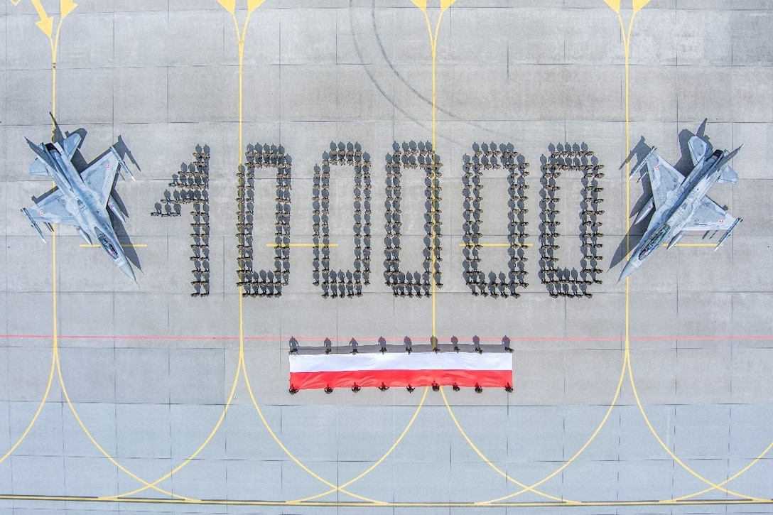 """The Polish Air Force celebrates 100,000 flight hours of its F-16 aircraft fleet, by staging a photo with its airmen standing in formation to form """"100000"""" when read from the sky. The airmen in the photo are accompanied by the Polish flag and two of the aircraft acquired from the United States. (Courtesy photo)"""