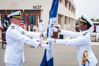 Cmdr. Jonathan Nieman, commanding officer of U.S. Naval Mobile Construction Battalion (NMCB) 3, passes the battalion colors.