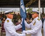 Cmdr. Ryan Carey (left) passes the battalion flag to Cmdr. Andrew Olsen.