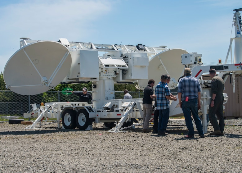 A group of men surround and provide maintenance on a Joint Threat Emitter.