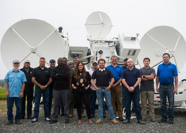 Group of men and women pose for a photo in front of a Joint Threat Emitter