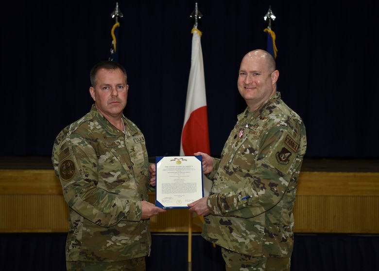 Two military members hold an award while posing for the camera.