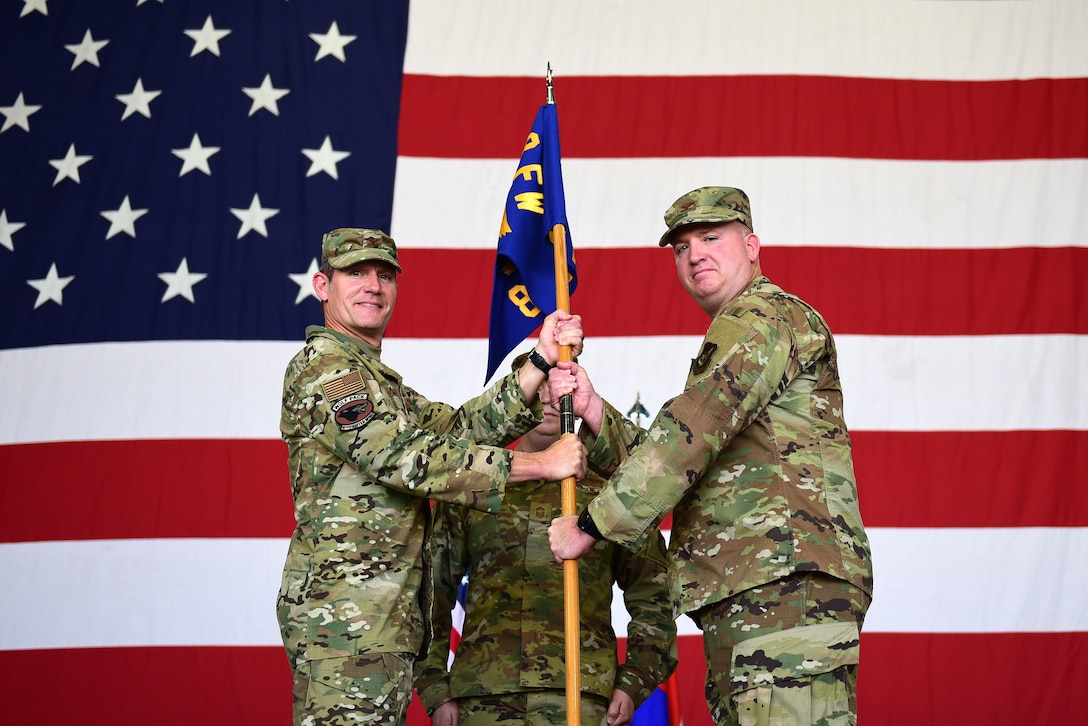 Two commanders pose for a photo during a ceremony.
