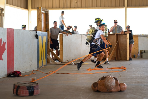A photo of an Airman pulling a fire hose
