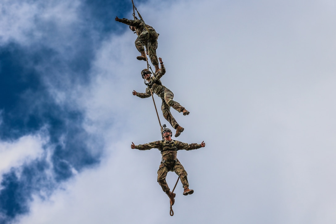 Three soldiers hang above each other on a rope in midair.
