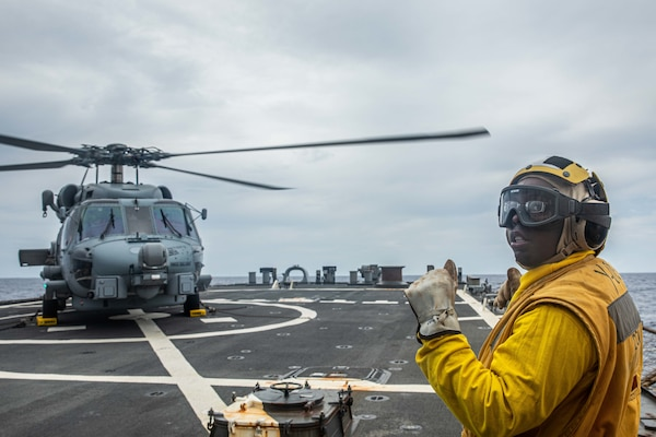Boatswain's Mate 2nd Class Daniel Branham, from Dalton, Ga., signals to an MH-60R Sea Hawk assigned to the Royal Australian Navy Anzac-class frigate HMAS Ballarat (FFH 155) on the flight deck of Arleigh Burke-class guided-missile destroyer USS Curtis Wilbur (DDG 54). Curtis Wilbur is assigned to Commander, Task Force 71/Destroyer Squadron (DESRON) 15, the Navy's largest forward-deployed DESRON and U.S. 7th Fleet's principal surface force. (U.S. Navy photo by Mass Communication Specialist 3rd Class Zenaida Roth)