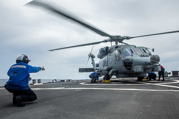 Sailors aboard Arleigh Burke-class guided-missile destroyer USS Curtis Wilbur (DDG 54) chock and chain a MH-60R Sea Hawk assigned to the Royal Australian Navy Anzac-class frigate HMAS Ballarat (FFH 155) on the flight deck. Curtis Wilbur is assigned to Commander, Task Force 71/Destroyer Squadron (DESRON) 15, the Navy's largest forward-deployed DESRON and U.S. 7th Fleet's principal surface force. (U.S. Navy photo by Mass Communication Specialist 3rd Class Zenaida Roth)