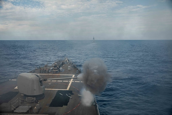 The Royal Australian Navy Anzac-class frigate HMAS Ballarat (FFH 155) steams ahead of Arleigh Burke-class guided-missile destroyer USS Curtis Wilbur (DDG 54) during a joint live-fire exercise. Curtis Wilbur is assigned to Commander, Task Force 71/Destroyer Squadron (DESRON) 15, the Navy's largest forward-deployed DESRON and U.S. 7th Fleet's principal surface force.
