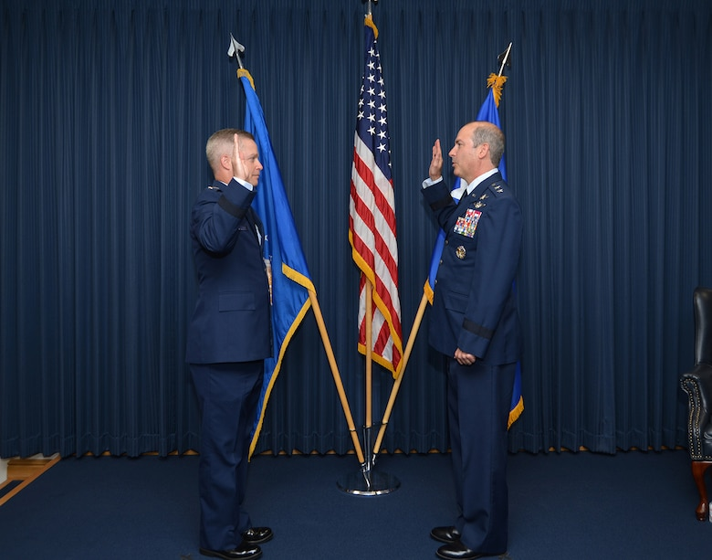 Two Airmen in dress uniform hold up right hands during the Oath of Office.