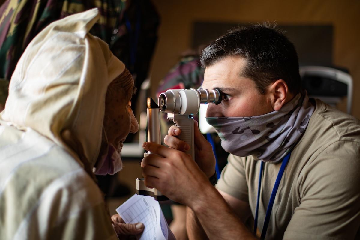An airman uses a small light to examine a man's eye.