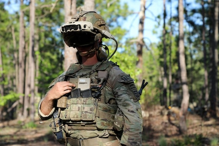 Photo of a soldier in a wooded area, wearing a mixed-reality headset during a training exercise.