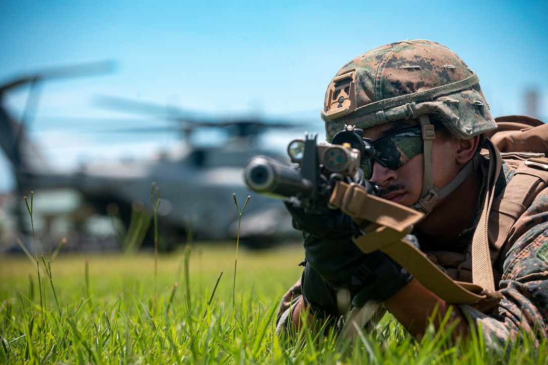 A U.S. Marine holds security after fast roping off of a CH-53E Super Stallion on Camp Hansen, Okinawa, Japan, June 3.