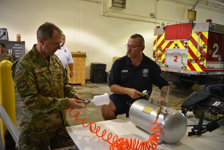 Chief Cadell looking at sprayer with Lt. Burgess