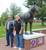 two veterans standing by blackjack statue