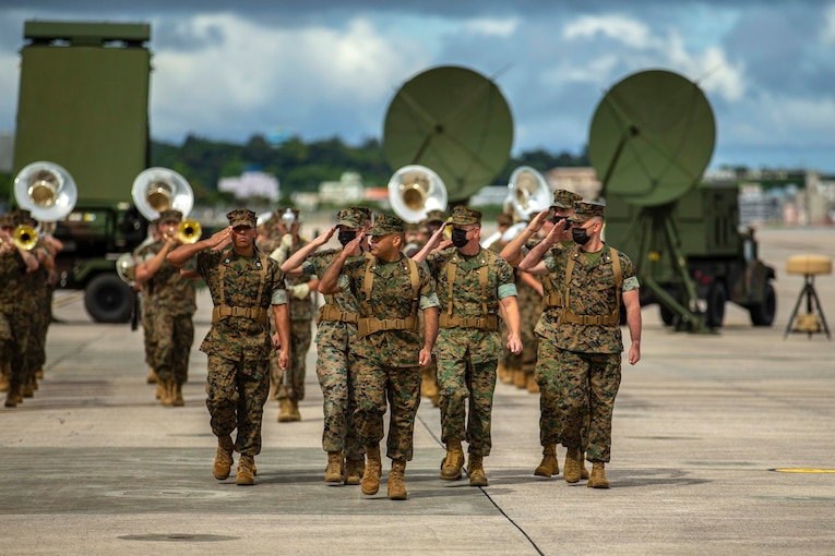 Marines salute while marching in formation.