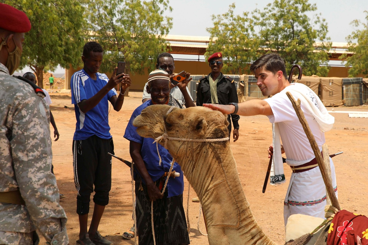 A soldier pets a camel as other peopole watch.