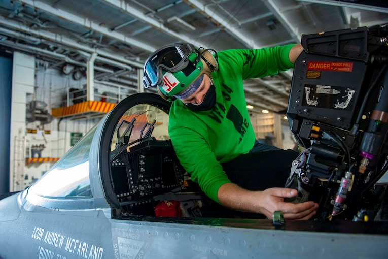 A sailor inspects the cockpit of a jet.
