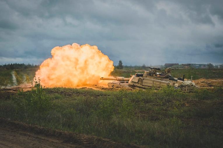 A tank fires in a field.